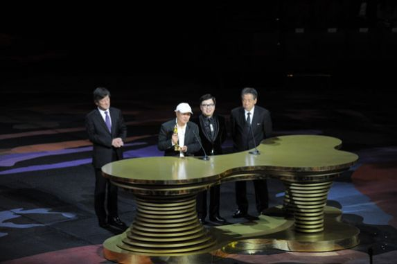 Actor Hou Hsiao Hsien receives the top honour at the 8th Asian Film Awards ceremony, the Lifetime Achievement Award, from the executive committee members of the AFAA